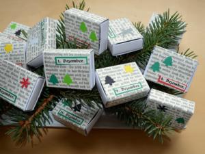DIY Adventskalender aus Streichholzschachteln mit Tannengrün auf einem Holzteller