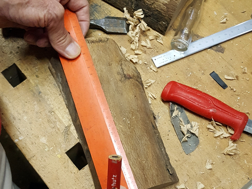 Kennzeichne Dir auf dem Holzscheit die Abstände der Bohrlöcher.