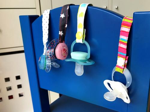 Der Schnuller kann am Ring am Schnullerband befestigt werden. Alternativ geht auch ein Haargummi für Schnuller ohne Ring.