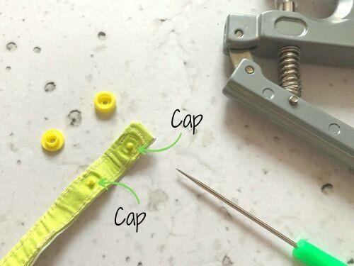 Stecke die Caps der Kam Snaps durch die Löcher.