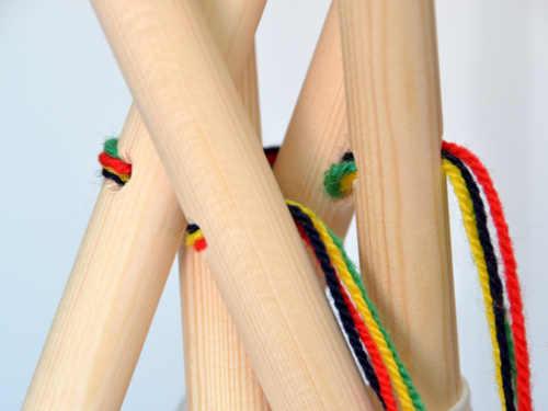Ziehe durch die Löcher der Holzstäbe deine Schnur oder Wolle.